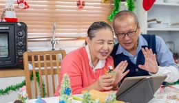 Senior-Asian-Couple-Using-Tablet-During-Holidays